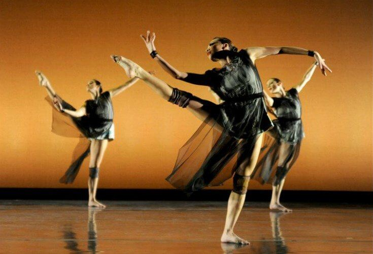 Three barefort ballet dancers dressed in black leotards with a tulle covering dance against a gold background