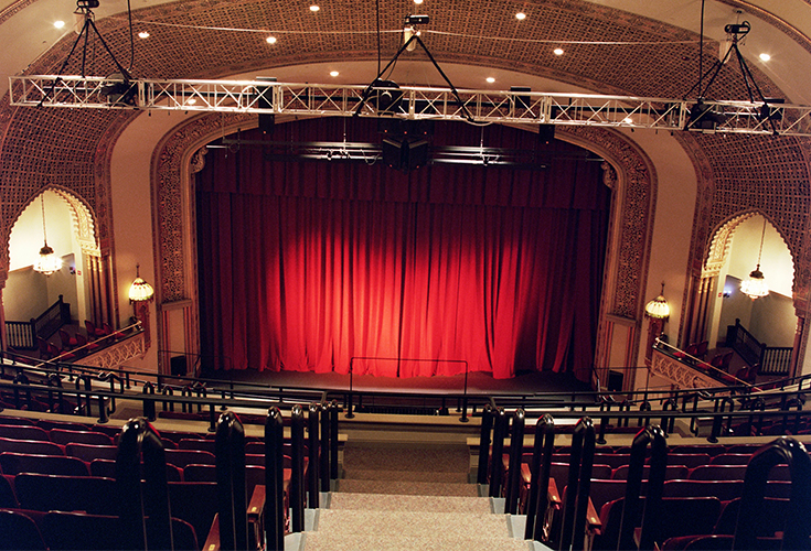 Center aisle view of the stage with curtain down before a performance