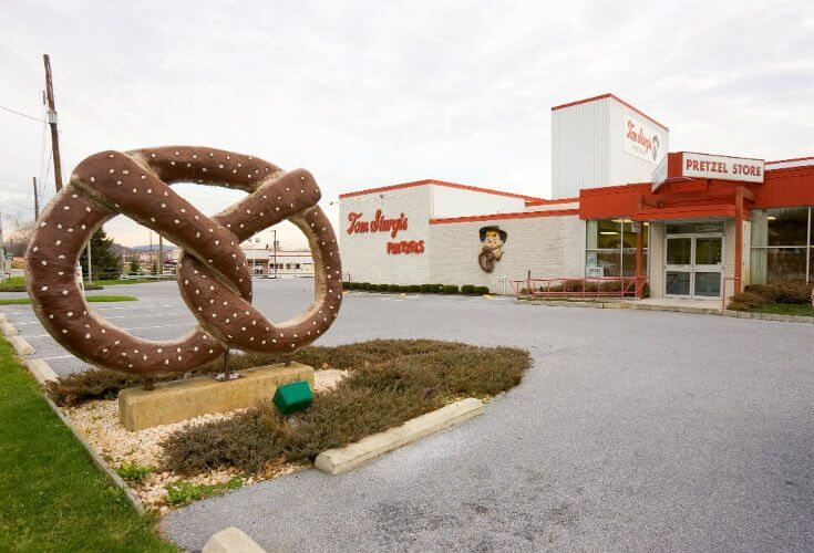The front of the Tom Sturgis Pretzel Factory with large pretzel in front.