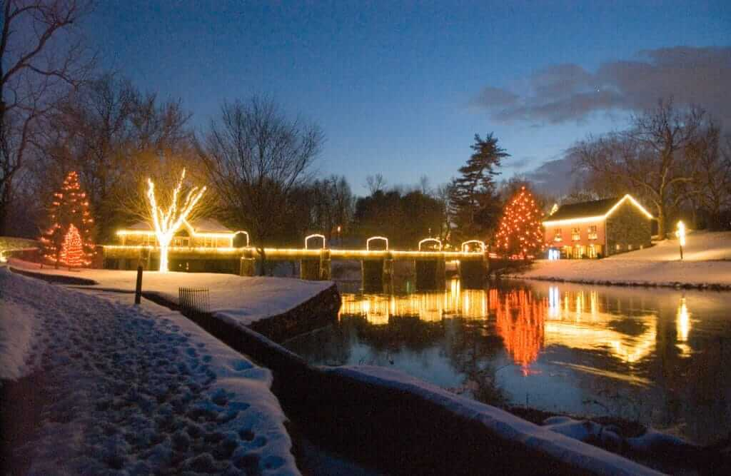 Thousands of holiday lights sparkle in the December night  on the trees, bridge, and buildings of Gring's Mill Park, and reflect in the Tulpehocken Creek.