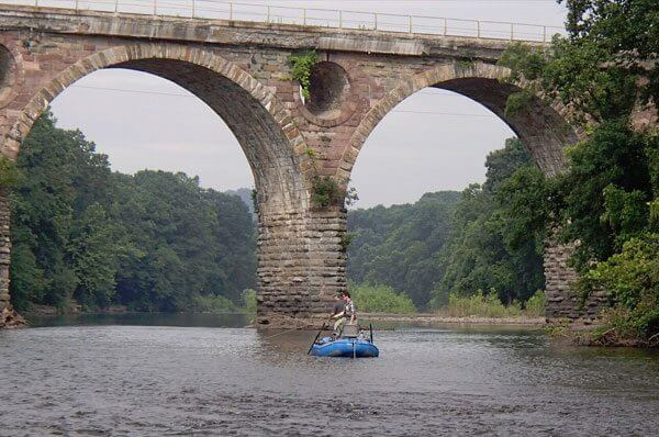Two fisherman standing in boat by Peacock's Lock Viaduct on Schuylkill River fishing.