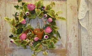 A leafy green wreath with pink flowers and a small clay plant pot hangs on a weathered door.