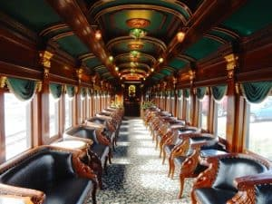 Wooden chairs with leather seats line the interior of a Colebrookdale Railroad car