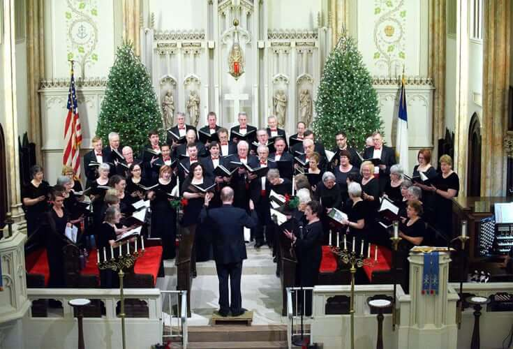 Men and women sing from their choral books in front of a church alter