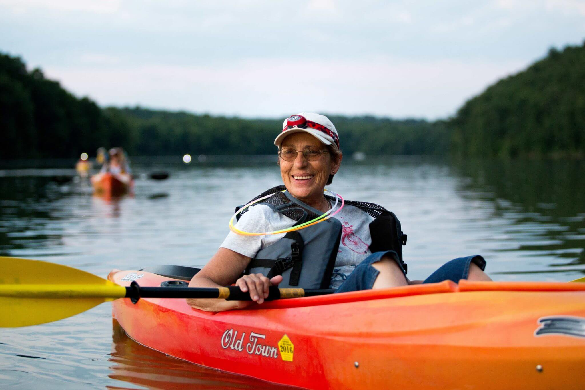 A happy woman sits in her orange kayak with glow-in-the-dark orbs around her neck as she participates in the Full Moon Kayaking event at Blue Marsh Lake.