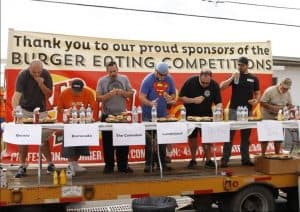 Seven men stand behind a table on the stage of Taste of Hamburg-er Festival. A plate of burgers sits in front of each man, which they are eating as they vie to win the Burger Eating Competition.