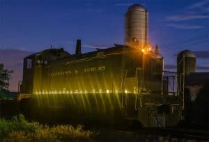 The Allentown & Auburn Railroad's engine at dusk with the headlight on and lights shining around the lower half of the train car.
