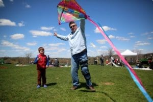 Father holding a kite with his small son excitedly looking on.