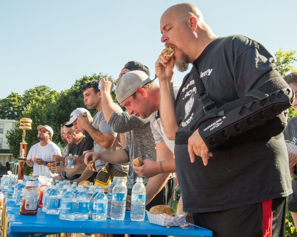 A close-up view of contestants in a hamburger eating contest at the Taste of Hamburg-er Fest.