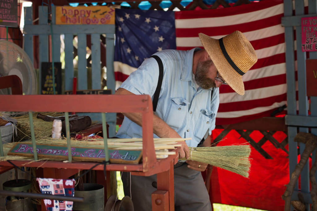 A man dressed as a farmer with a large brimmed hat, blue shirt, and pants with suspenders bundles straw for a broom he is making at the Kutztown Folk Festival