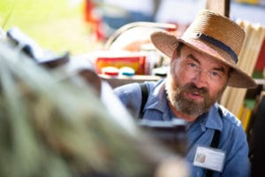 An older, bearded man dressed in typical PA Dutch attire, large brim straw hat peaks out from behind a blurred object. His blue work shirt and suspenders are visible.