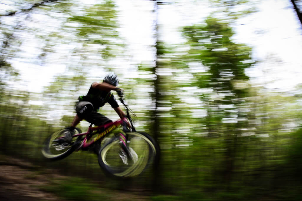 A mountain biker catching some air as he rides his bicycle downhill on Greater Reading Trails System