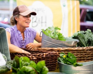 A woman sells fresh lettuce and other green vegetables at a stand at the Leesport Farmers Market in Berks County