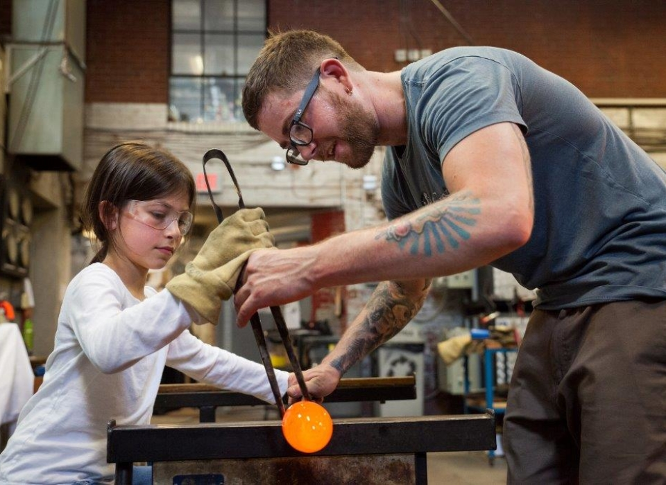 A young girl is helping a glass blower with his demonstration at GoggleWorks Center for the Arts.