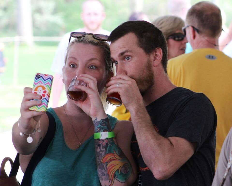 Attendees of the Boone Beer Fest, a man and a woman, take a selfie of themselves as they sample craft beers.