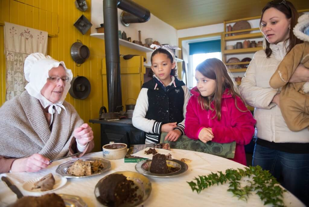 Children watch as a woman seated at a table and dressed in 18th century garb, talks about early PA Dutch holiday treats.