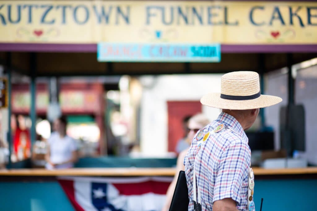 A man dressed in a blue and purple plaid shirt with a wide brimmed straw hat walks in front of the Funnel Cake Stand at the Kutztown Folk Festival in Berks County, PA