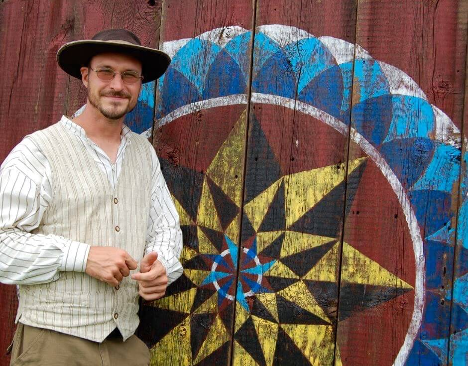 Patrick Donmoyer, local hex barn art expert, stands in front of a colorful hex symbol painted on a red barn.