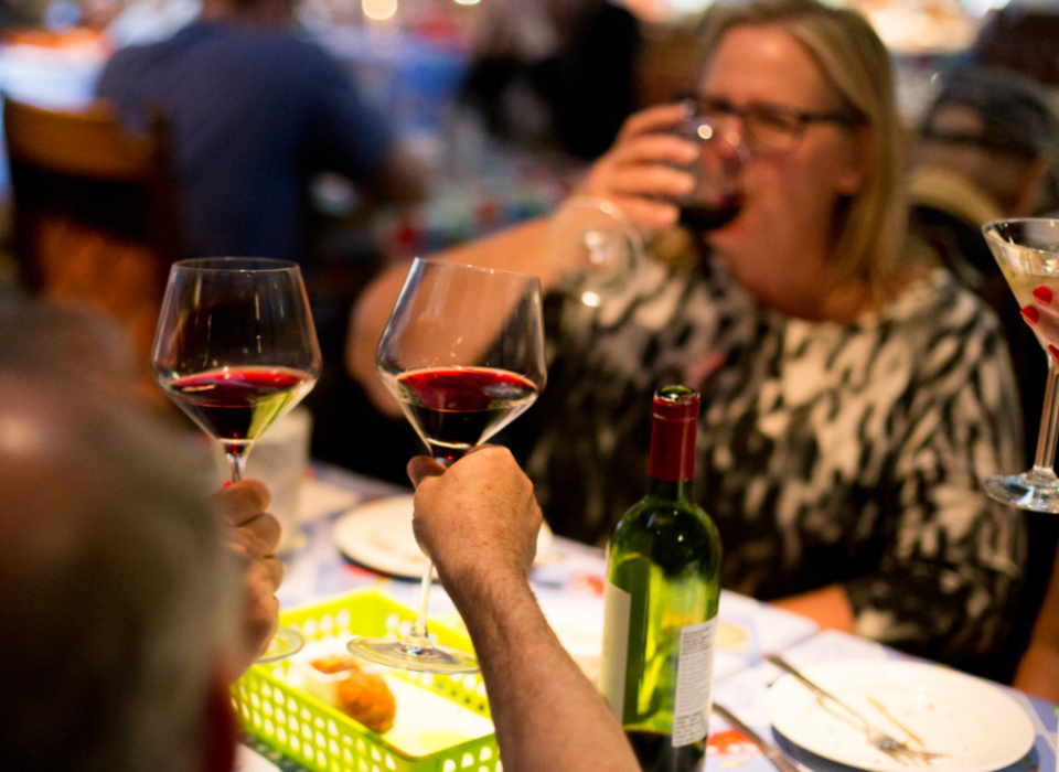 Three diners toast each other with glasses of red wine at Judy_s on Cherry Restaurant in Reading, PA.