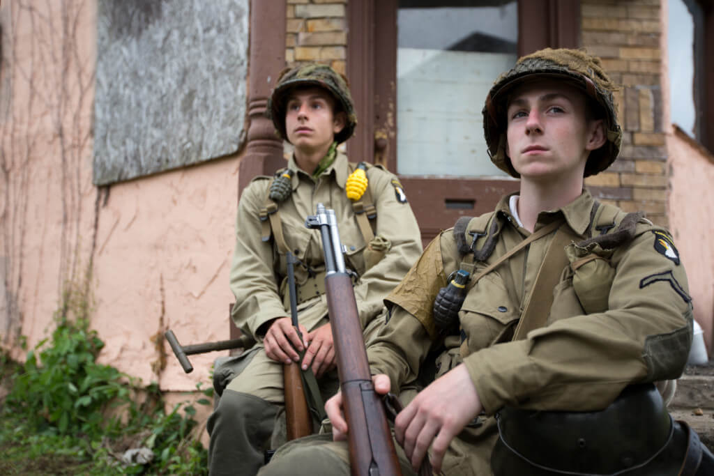 Young men in their late teens or early twenties are dressed as GIs at MidAtlantic Air Museum_s annual World War II Weekend.