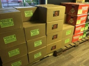 Brown boxes filled with different kinds of Saucony Creek Beer are stacked and ready for delivery.