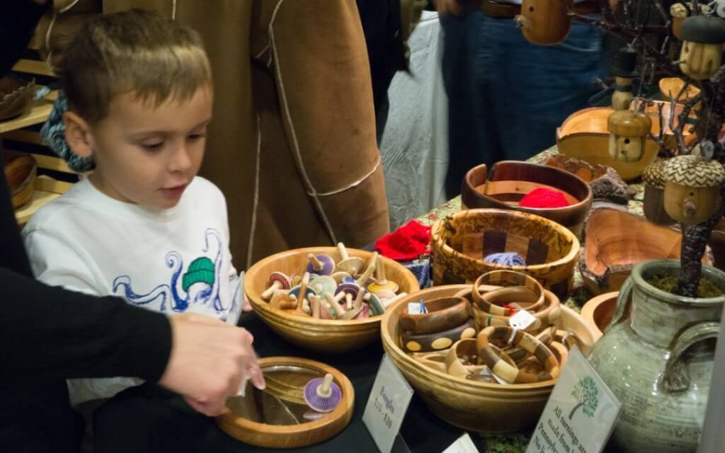 A young boy looks at wooden bowls filled with wooden toys and bracelets at a holiday craft show.