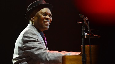 A black man, jazz pianist Booker T. Jones sits at a piano.