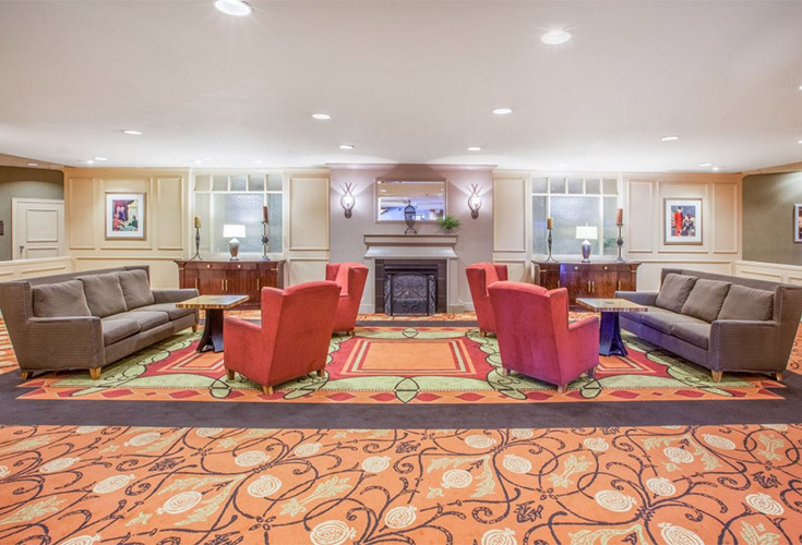 Beautifully decorated Lobby area of the Radisson Hotel with soft orange wing back chairs, charcoal couches and colorful rug