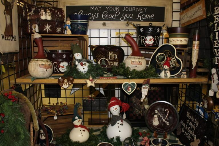 Shelves decorated for Christmas and filled with handmade Christmas gourd santas and snowmen at a holiday craft show.
