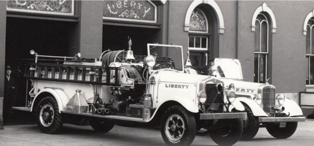 A black and white photograph of two vintage fire trucks parked in front of the Liberty Fire Company in Reading, PA, now home to the Reading Area Firefighters Museum.