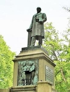A statue of a standing President McKinley, wearing a green patina, stands atop a tall concrete base with tree tops in the background. The base of the statue has a plaque and a picture on it, also patinaed with age.