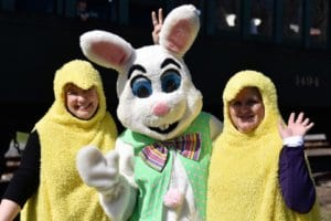 """The Easter Bunny is flanked by two women dressed in """"Peep"""" Chick costumes."""