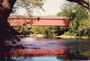Wertz Covered Bridge's red facade can be seen in the distance. Trees surround the bridge and the water it crosses.