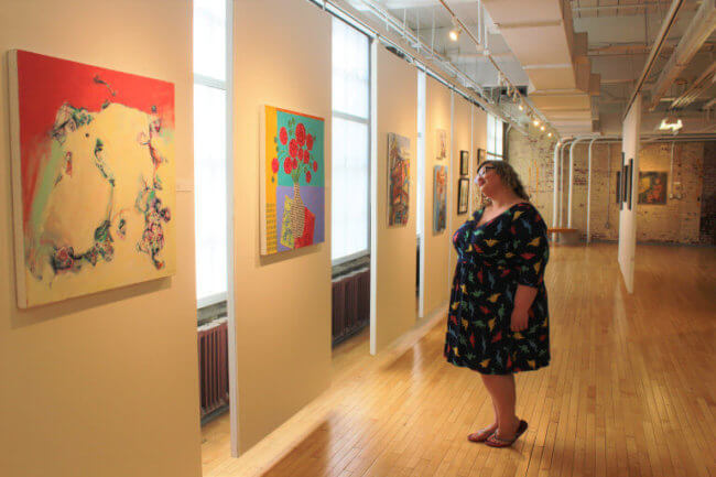 Woman in a blue dress looks at art in a gallery at the GoggleWorks.
