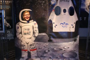 A woman pokes her head through a cutout atop a cardboard astronaut to give the figure her face at the museum.