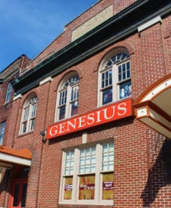 The red Genesius Theatre marquee sits below 2 arched windows on the front of the theatre.