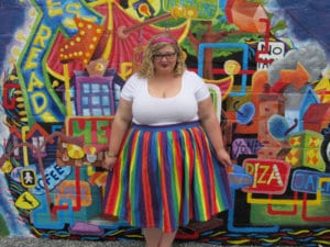 Young woman stands in front of a colorful outdoor wall mural