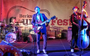 Three musicians stand in front of a Berks Country Fest banner as they play their instruments, the guitar, bass and drums.