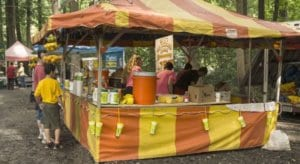 A lemonade, decked out in yellow and orange striped canvas, sits along a wooded path at Muhlenberg RiverFest.