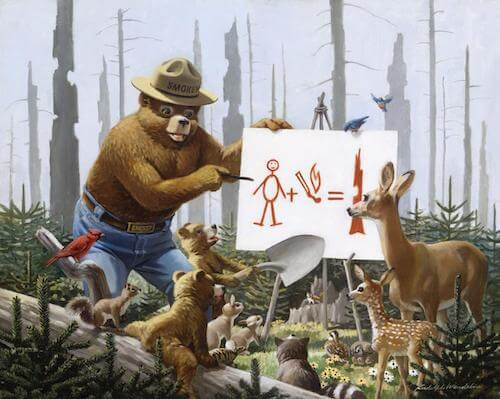 An illustration of Smokey the Bear depicts the National Park's mascot educating forest creatures of the dangers of fire with a drawing.