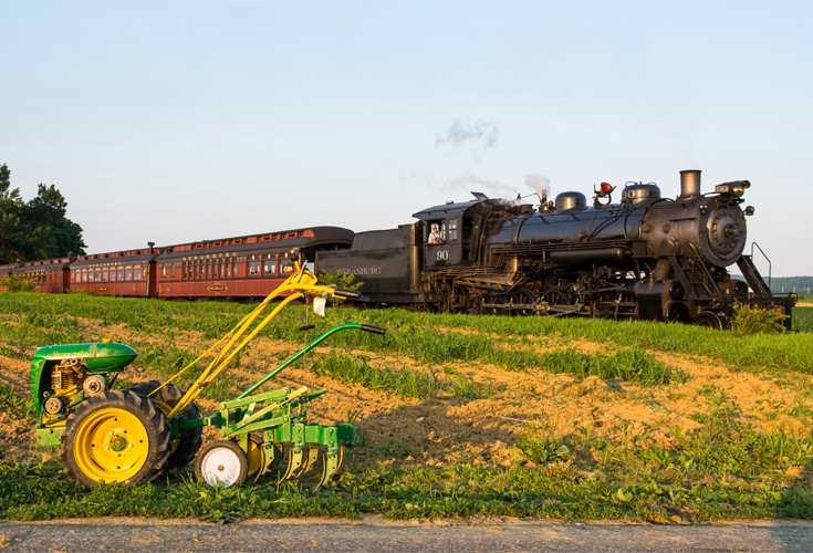 A Strasburg Rail Road steam locomotive rolls passengers through Amish farmland