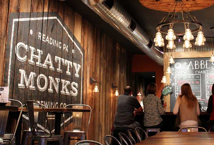 A tap at Chatty Monks is pictured with the brewery's logo painted behind it and people sitting in at a bar in the background.