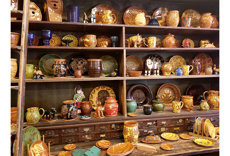 Colorful pottery from Robesonia Redware line the shelves at their shop