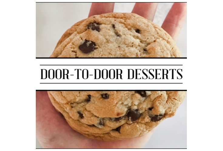 Chocolate chip cookie rests in a hand with the words Door-To-Door Desserts written on top in a white banner