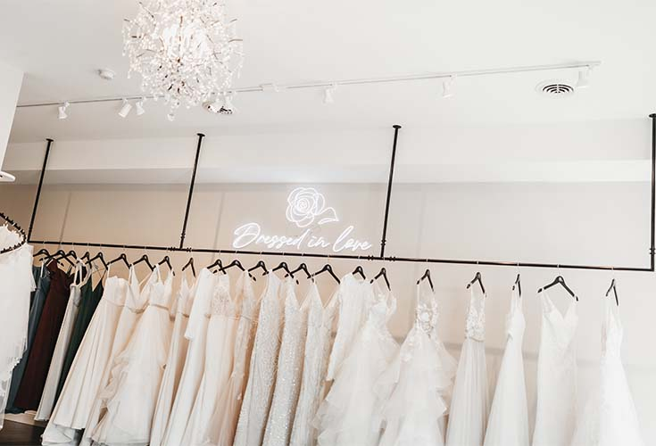 White Wedding Gowns line the wall at Dressed in Love Bridal Shop