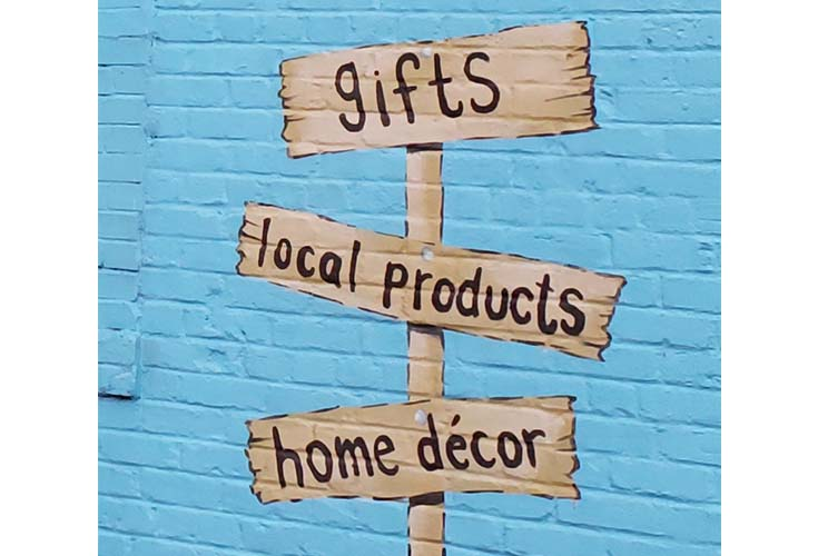 3 brown signs on a pole with a blue brick background on the signs are written gifts, local products and home decor