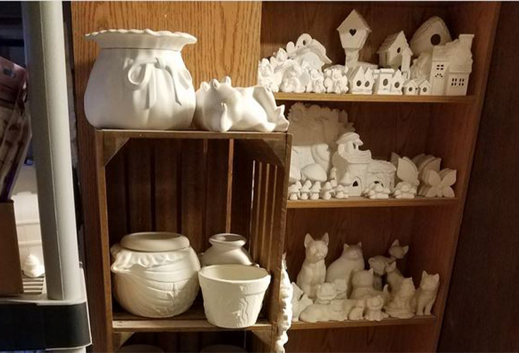 Bisque ceramic pieces sit on shelves waiting to be painted