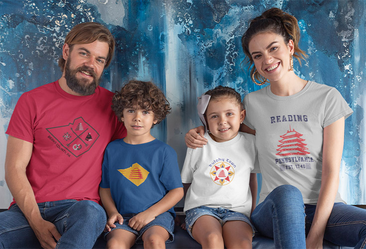 2 Children and their mother and father sit against a blue backdrop. All 4 are wearing T-shirts depicting Berks County and the Pagoda